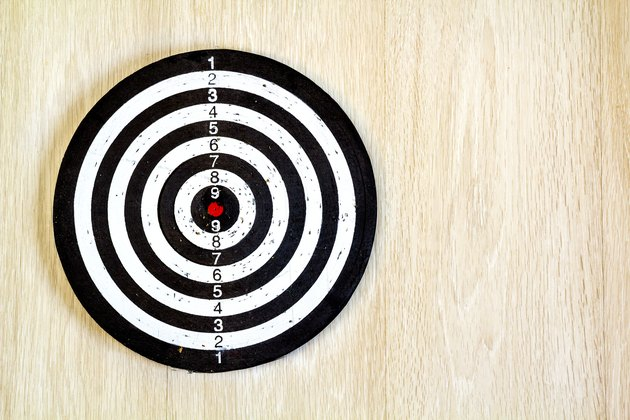 Black and white target dart on wooden background. Top view.