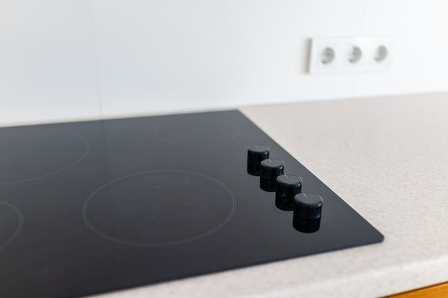 Closeup and knobs on modern luxury electric cook stove top stovetop cooktop with glass reflection and circles background in empty home