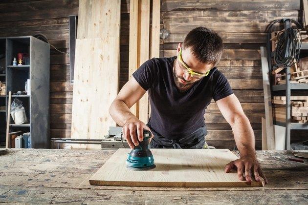 carpenter polishes wooden board