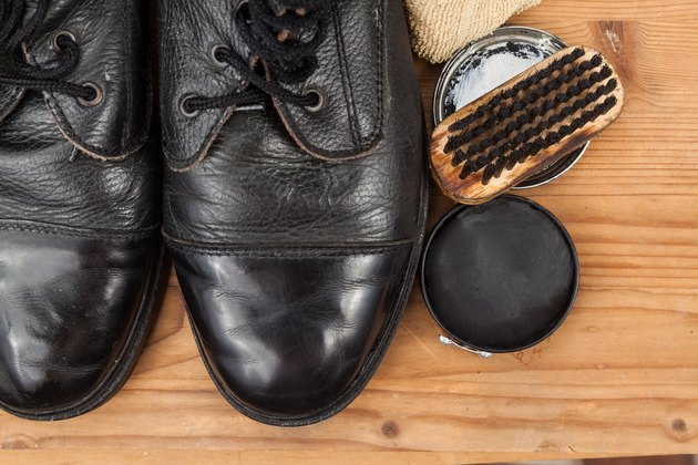 Shoe polish with brush, cloth and worn boots on platform