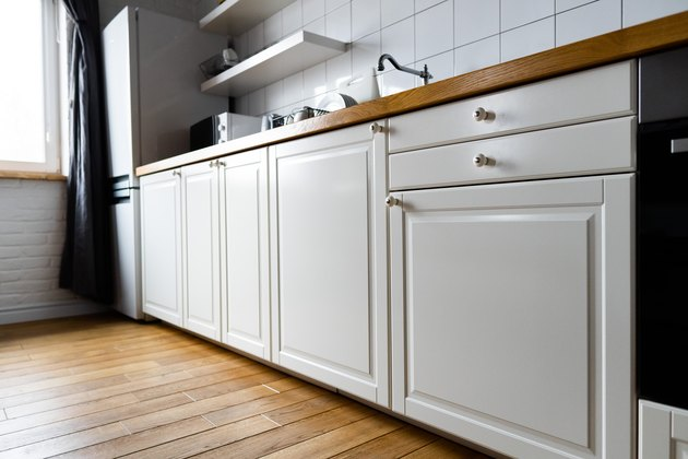 Appliances and furniture: bright white cabinets with wooden countertop, electric cooker, induction hob, faucet, sink and dish rack against hardwood floor and light tile in modern scandinavian kitchen