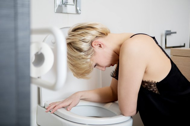 Young Woman Leaning In Toilet Bowl