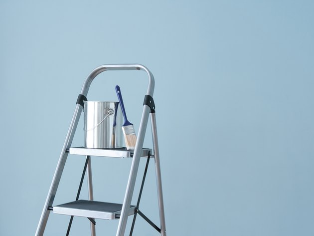 Stepladder holding paint can.