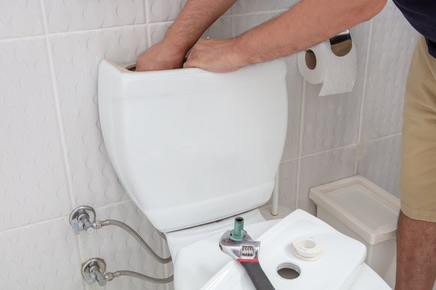 Man using hands repairing toilet cistern