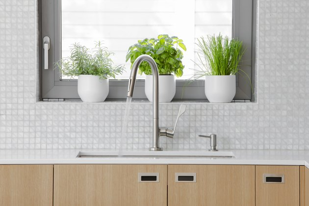 Modern kitchen Stainless steal faucet with water running into sink.