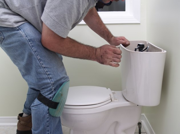Plumber at work repearing toilet