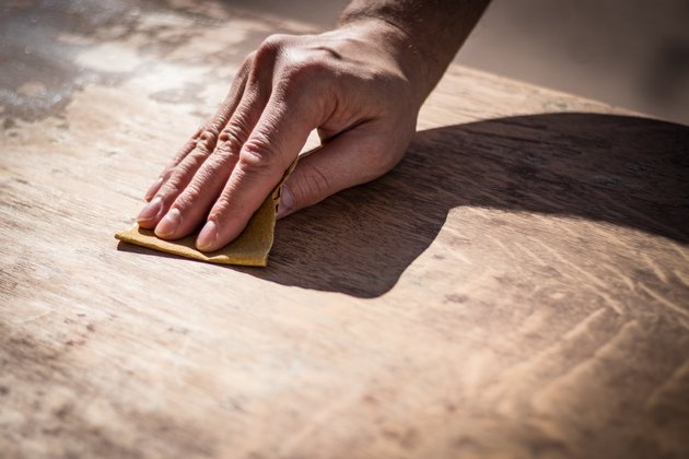 Gritty weathered man's hand sanding a wooden surface