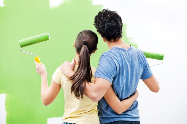 Young couple painting the wall.