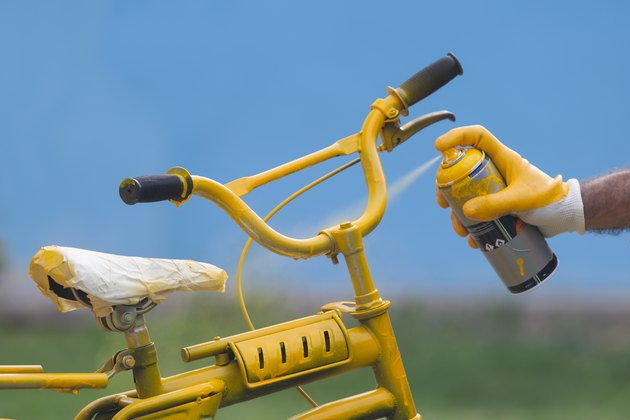 Photo of yellow bike painting with yellow glove