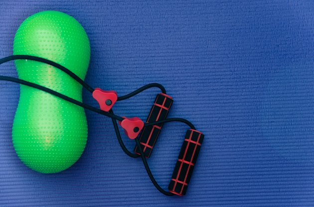 Rubber resistance bands and small peanut shaped exercise ball at fitness mat.