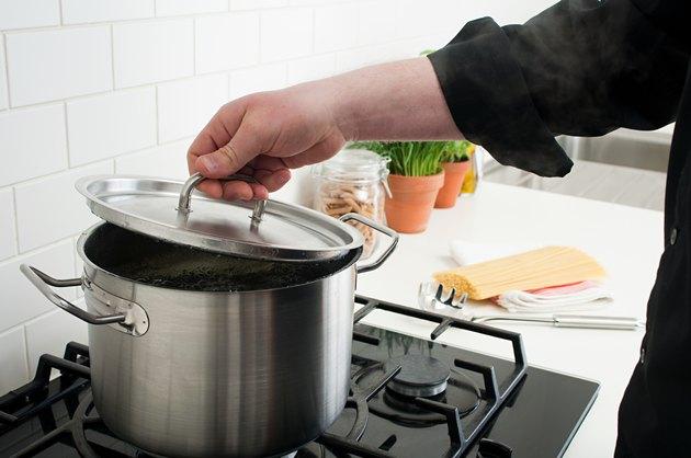 Man lifting lid on saucepan