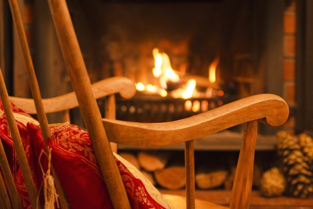 Wooden rocking chair and the fireplace interior at home. Winter weekend. Evening on Christmas holiday. Interior design.