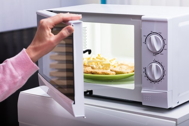 Woman Heating Fried Food In Microwave Oven