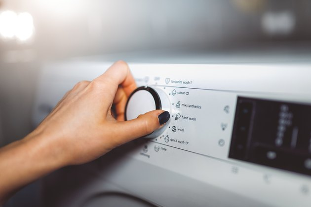 Woman choosing program on washing machine