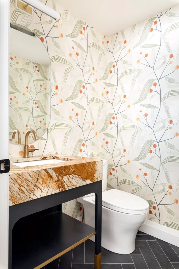 powder room with botanical wallpaper and marble sink with deck-mounted faucet