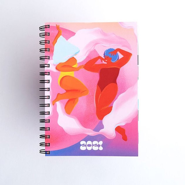 spiralbound planner with colorful artwork of two women