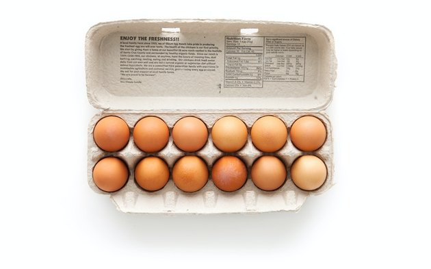 brown eggs in egg carton on white background