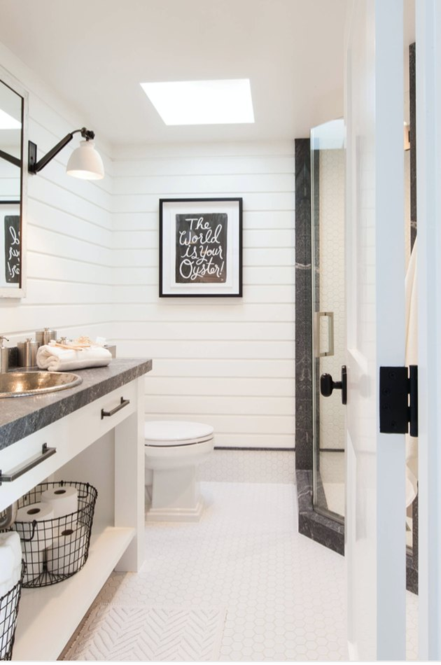 stainless drop in bathroom sink with white shiplap walls