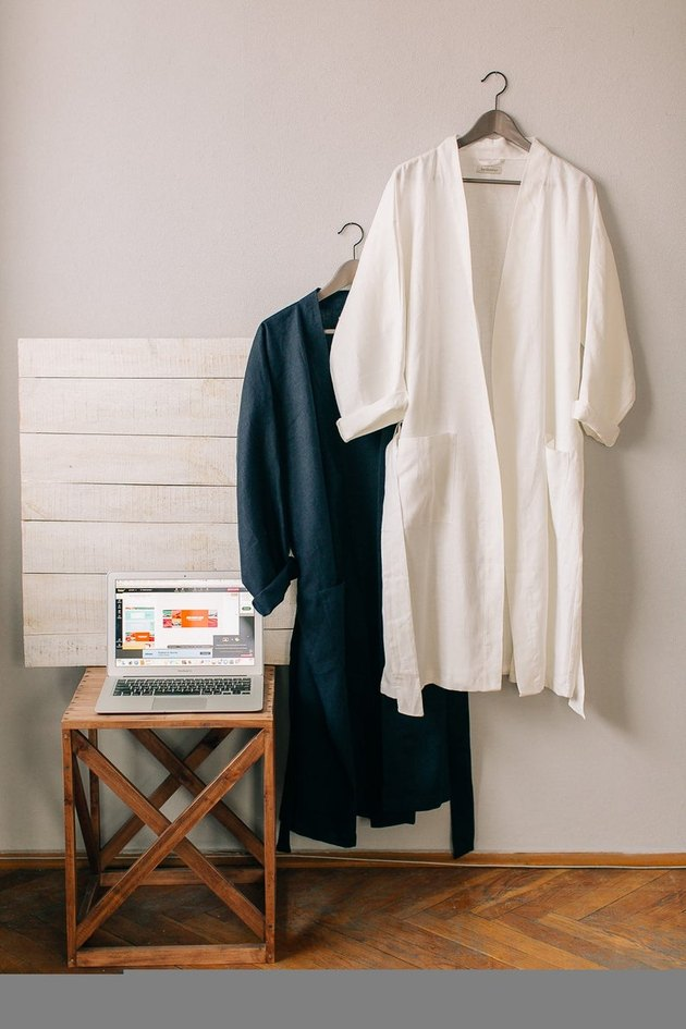two robes hanging near wood stool with laptop