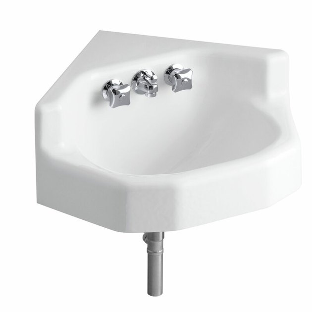 White cast iron wall mount corner bathroom sink with silver fixtures