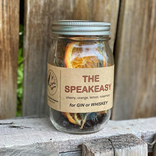 """mason jar with ingredients and label that reads """"the speakeasy"""""""
