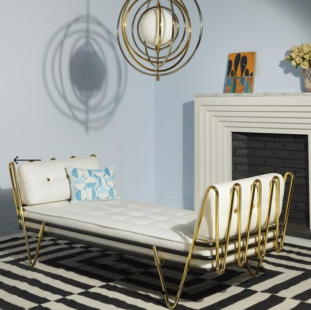 Small Space Daybed Ideas with Brass daybed, striped rug, brass pendant lamp, mantle.