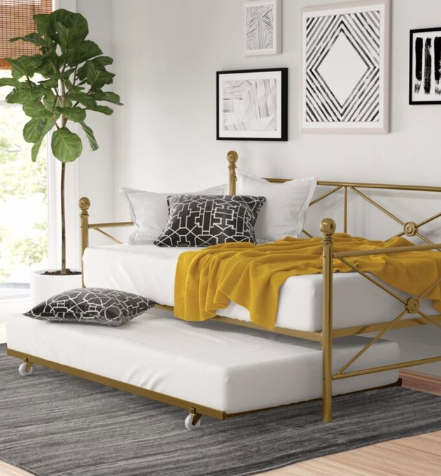 Small Space Daybed Ideas with Brass trundle bed with yellow blanket, pillows, plants, art, rug.