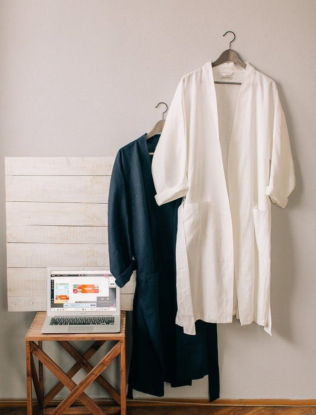 two robes hanging near a table with laptop