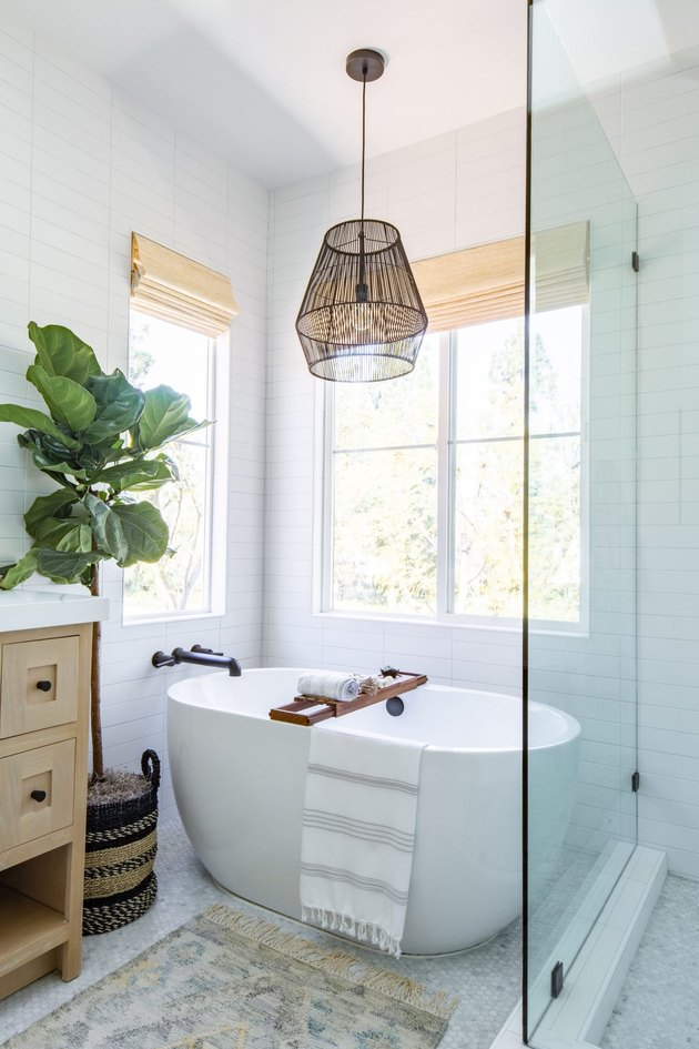 white modern bathroom with freestanding tub and black tub fixtures, woven lamp hanging above and next to it, a glass shower door