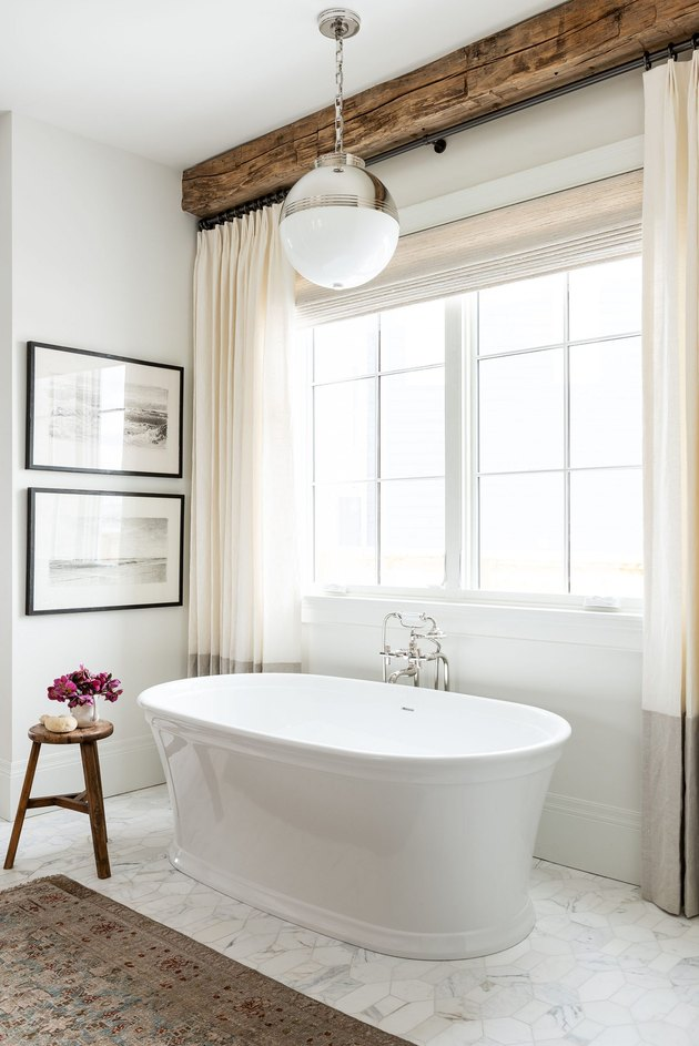 freestanding tub with traditional bath fixtures and wood beam ceilings