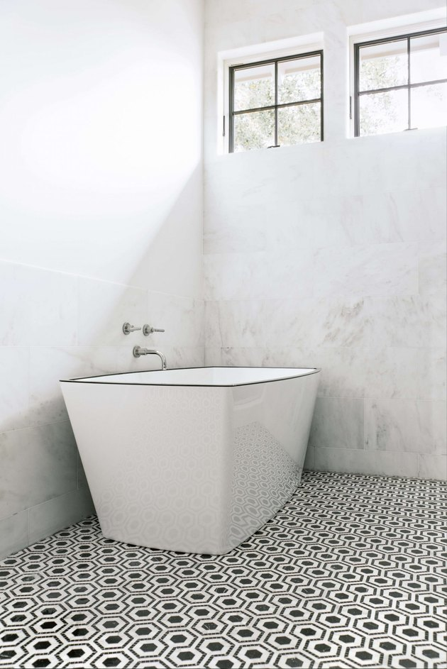 modern bathtub fixtures in marble bathroom with freestanding tub and two windows above it