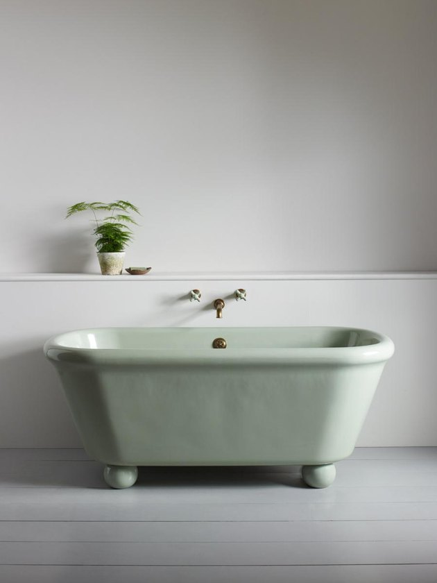 modern bathtub fixtures with green tub in a gray room