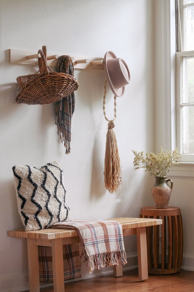 DIY wooden peg rail hanging above bench with baskets, scarf and hat hanging from pegs
