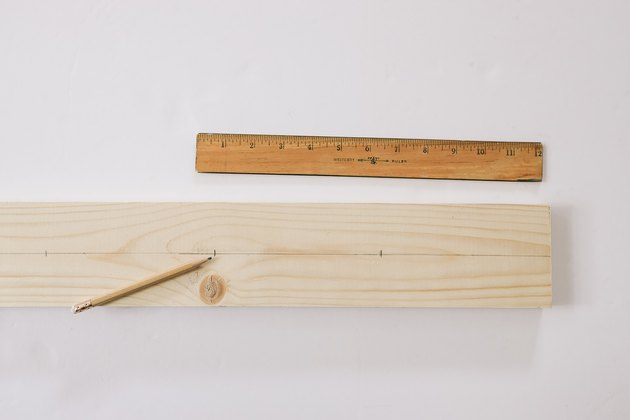 Line drawn down center of wood board with marks for peg spacing