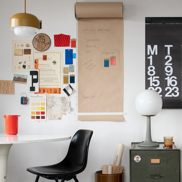 modern home office with black office chair and colorful papers and calendar on the wall