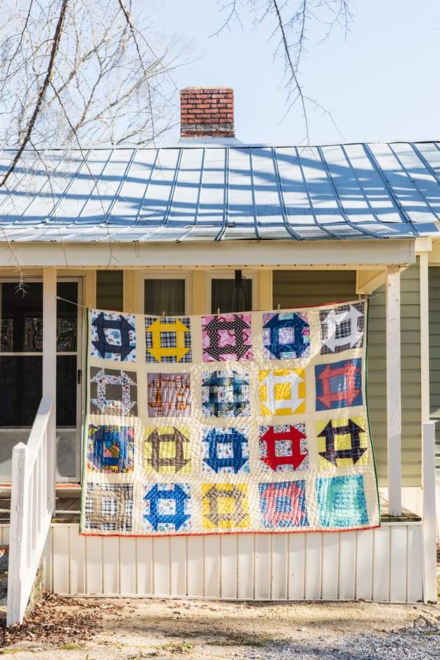 multicolored quilt hanging in front of a house