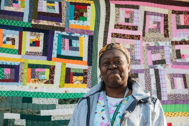 woman standing in front of quilt