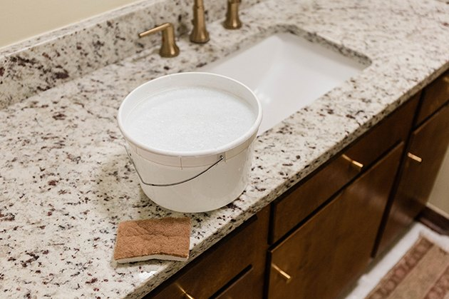 Wash down the cabinet doors and surround using soapy water and a sponge.