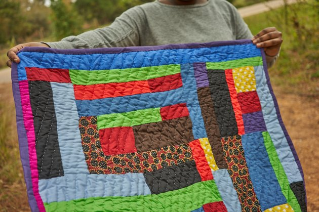 woman holding colorful quilt