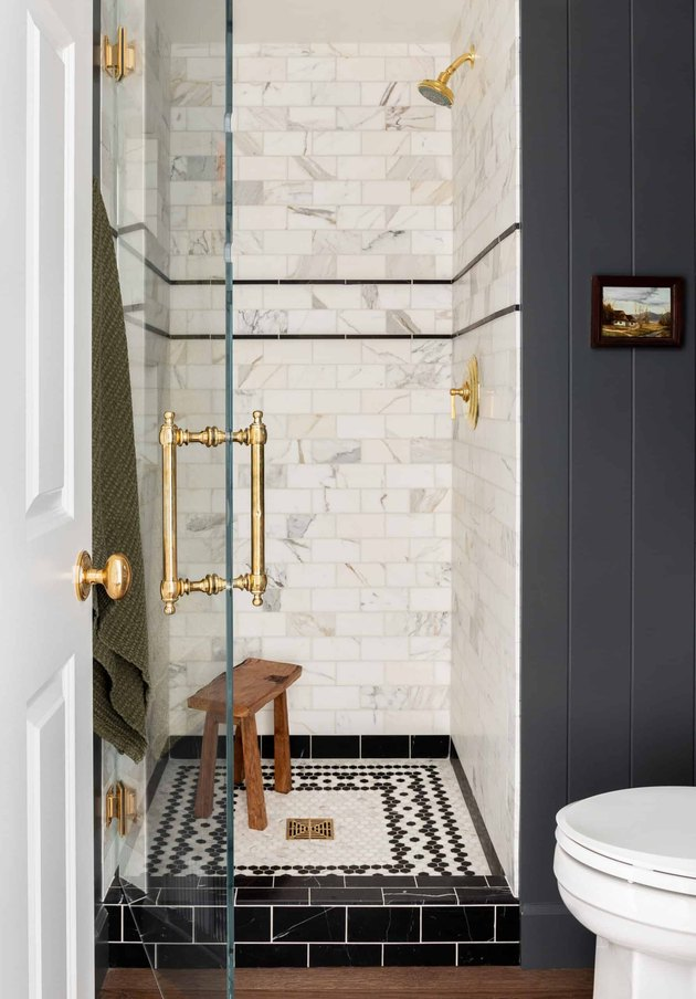 traditional shower fixtures in black and white bathroom with brass fixtures