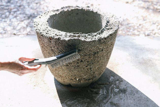 Scrubbing sides of hypertufa planter with wire brush to rough up surface