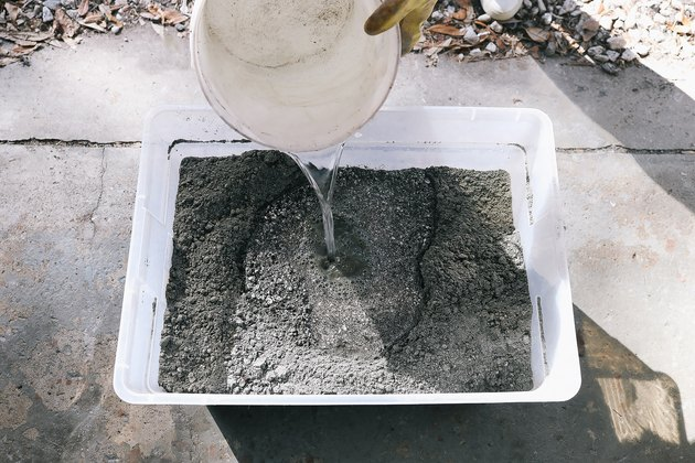 Pouring water into storage bin with hypertufa mix