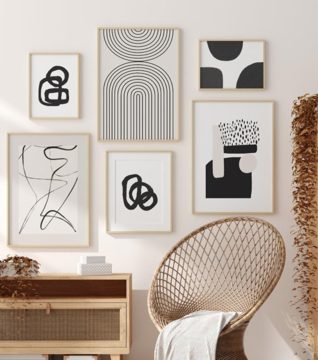 Hallway Gallery Wall Ideas with prints, art, wicker chair, credenza, blanket.