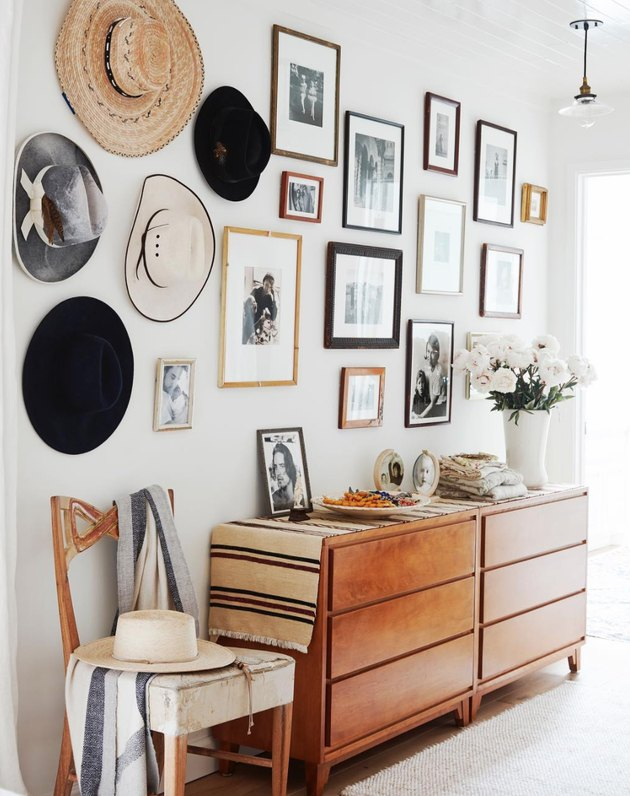 Hallway Gallery Wall Ideas with credenza, photos, prints, hats, chair, flowers.