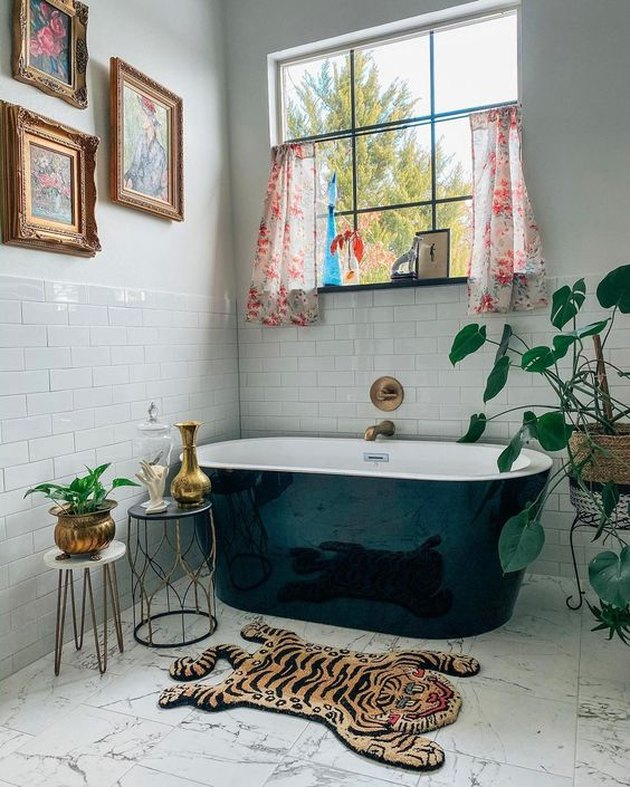 Sarisa Munoz The Indigo Leopard Home bathroom with red floral chandelier and black freestanding tub