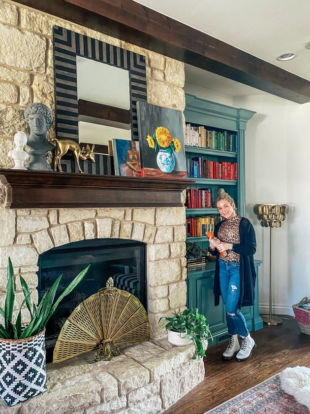 Sarisa Munoz of The Indigo Leopard Home standing in front of stone fireplace