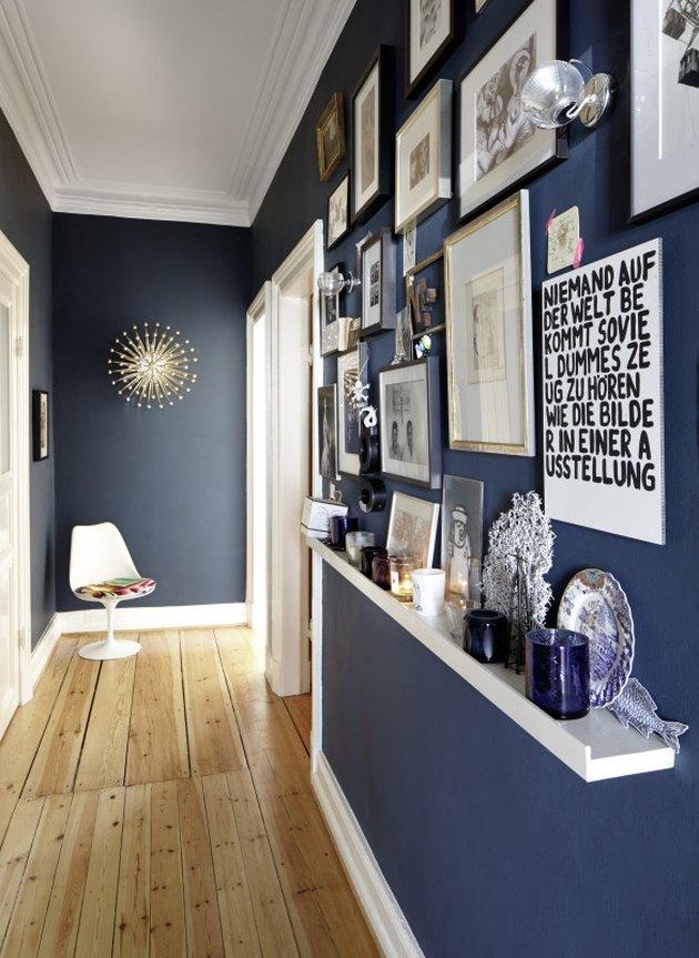 Hallway Gallery Wall Ideas with prints, art, shelf, accent chair, wood floor.