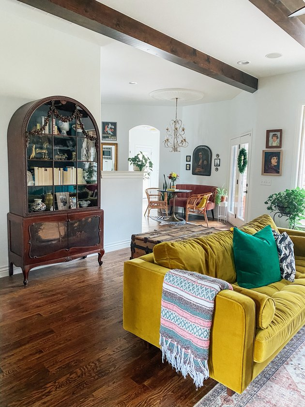 Sarisa Munoz The Indigo Leopard Home living room with mustard yellow velvet sofa and vintage cabinet