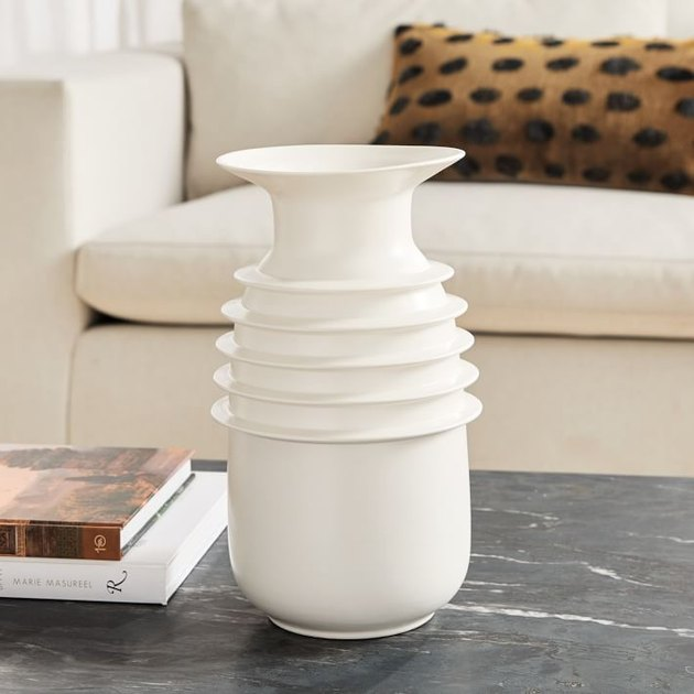 ivory sculptural vase near white couch