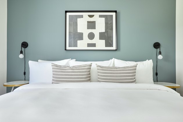 White bed against sage green wall